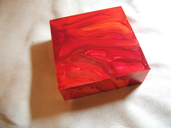 a piece of cradled panel coated with a swirl of acrylic paint in hot colors