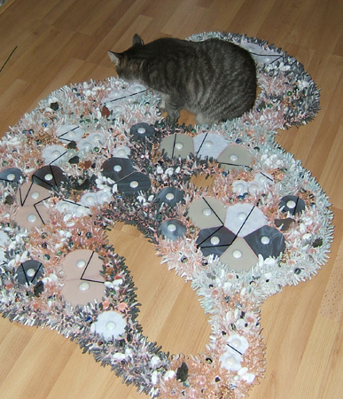 A cat sniffing a mosaic by Lynn Bridge