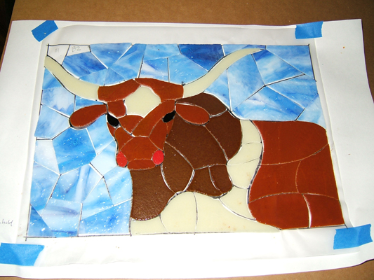 fitting cut tesserae onto the longhorn drawing